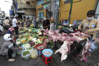 Local vendors sell pork meat and vegetables on a sidewalk as the main market remained closed during a lockdown in downtown Phnom Penh, Cambodia.