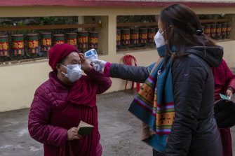 A Tibetan Buddhist nun has her temperature checked at the polliing station in Dharmsala, India on Sunday.
