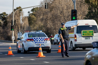 Victoria Police stop cars entering The Causeway at a checkpoint between Albury and Wodonga on Sunday.