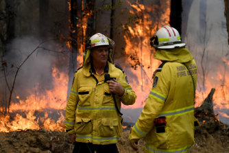 NSW Rural Fire Service crews talk as flames burn in the background.