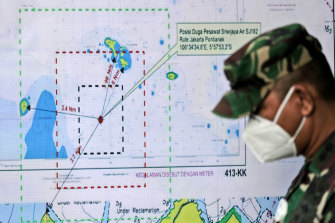 An Indonesian soldier walks past a map showing the location where a Sriwijaya Air passenger jet lost contact with air traffic controllers.