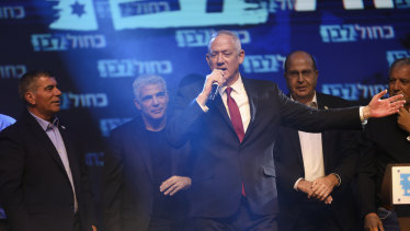 Blue and White party leaders, from the left, Gabi Ashkenazi, Yair Lapid, Benny Gantz (with the microphone) and Gabi Ashkenazi greet their supporters at party headquarters after the first results of the elections in Tel Aviv.