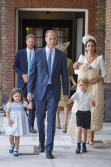 Princess Charlotte and Prince George hold the hands of their father Prince William while Kate, Duchess of Cambridge holds Prince Louis as they arrive for his christening service.