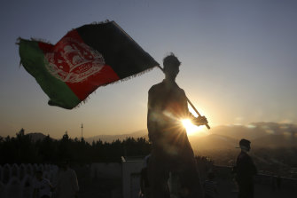 A man waves an Afghan flag in Kabul, Afghanistan, in August last year. In February, Afghanistan reported multiple American military deaths after an insider attack by a man wearing an Afghan army uniform.