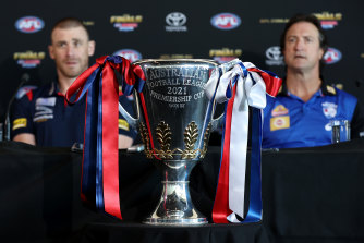 Melbourne coach Simon Goodwin and Bulldogs counterpart Luke Beveridge flank the premiership cup on Friday.