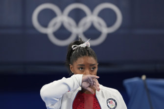 Simone Biles watches on after exiting the team final.
