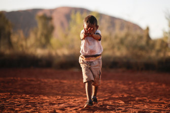 A boy plays while waiting for celebrations marking the closure of the Uluru climb.