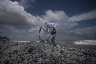A Sri Lankan navy soldier clad in a protective suit walks on the mounds of debris washed ashore from the burning Singaporean ship on Thursday.