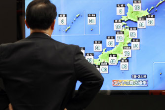 A man watches a TV weather forecast on Friday ahead of the typhoon's expected arrival on Saturday.