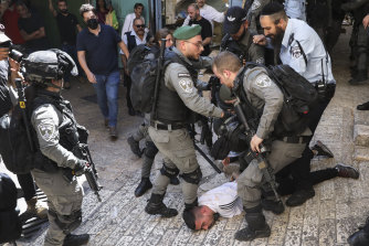 Israeli police officers detain a Palestinian youth during a protest against Israel's air strikes on the Gaza Strip and the violent confrontations between Israeli security forces and Palestinians, in Jerusalem's Old City on Tuesday.