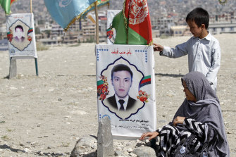 An Afghan woman sits by her son's gravee on the outskirts of Kabul as the peace talks began last year.