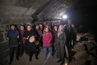 Director Sue Johnson (holding the drum) with her choir, the Trolls, singing under the Murray Road bridge in Coburg.