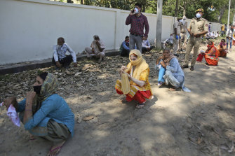 People squat as they wait outside a bank to withdraw money during lockdown on the outskirts of Jammu, India.