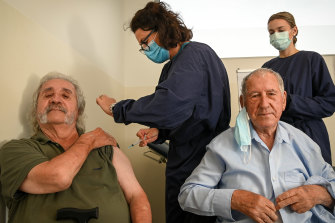 John Manolakakis and his father Jim receive their shots at Altona North Respiratory Clinic on Monday, administered by nurses Peirrene McConville (left) and Chloe Coffin.