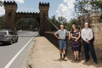 Kangaroo Valley residents Gary Moore, Kate Watson and Matt Gray near the town's Hampden Bridge. The wooden structure is the sole bridge across the Kangaroo River and carries a major water pipe.