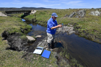 Professor Geoffrey Hope of the Australian National University examines the pH of the water near Yarrangobilly in Kosciuszko National Park.