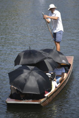 People shelter from the sun under umbrellas as they take a punt ride on the river Cam at Cambridge, England.