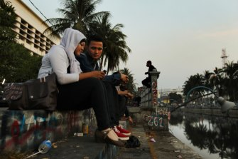 A couple sit by a Dutch-built colonial-era canal in Jakarta in 2012.