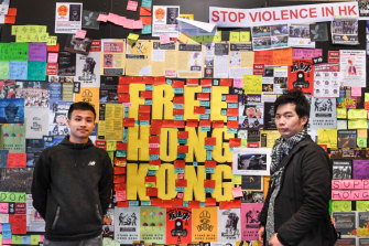 Dennis Chui, left, and Silver Lee stand with the Lennon Wall they helped construct at the University of Technology, Sydney.