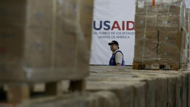 A man walks past boxes of USAID humanitarian aid at a warehouse at the Tienditas International Brigde on the outskirts of Cucuta, Colombia.