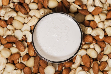 Glass of almond milk, surrounded by a mixture of almonds, cashews and macadamia nuts.