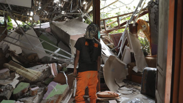 A rescuer inspects a damaged house at a village hit by a landslide in Nganjuk, East Java.