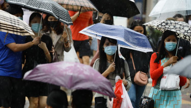 Protected but not over-protected: masked people in the rain in Singapore.