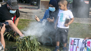 Sabah Siyad and her son Saami participates in a smoking ceremony at the rally.