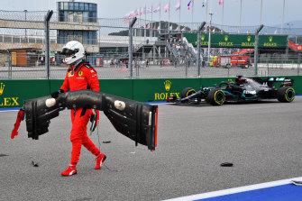 Sebastian Vettel retrieves his front wing as Hamilton drives past.