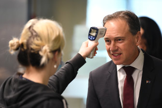 Federal Health Minister Greg Hunt has his temperature checked before touring the Royal Melbourne Hospital on Thursday