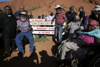 Traditional Owners pose for photos after placing the new sign of the permanent closure.
