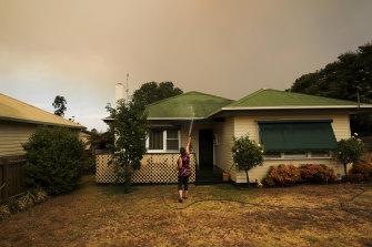Bruthen resident Janine Pratt hoses down her home as burnt leaves fall on the property.