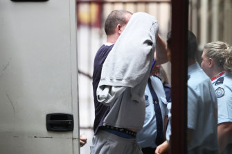 Scott Murdoch covers his face as he arrives at court on Monday.