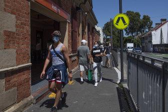 Sydneysiders wearing masks outside Redfern Station.