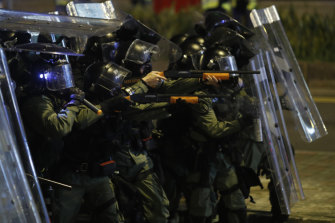 Riot police officer point weapons during a confrontation with protesters in Hong Kong on Sunday.