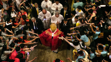 Francis walks out from Assumption Cathedral as Thai youth reach out to touch him in Bangkok on Friday.