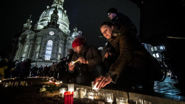 People arrive to light candles next to Frauenkirche cathedral to commemorate the victims of the 1945 Allied firebombing of the city on the 75th anniversary of the bombing in Dresden, Germany.