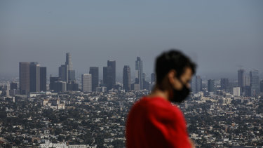 A man wears a face mask while visiting the Griffith Observatory overlooking downtown Los Angeles.