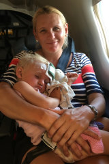 Larissa Petfield cradles her 18-month-old daughter Clare on the Royal Flying Doctor Service flight.