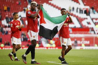 Duo Manchester United Paul Pogba dan Amad Diallo memegang bendera Palestina setelah bermain imbang 1-1 dengan Fulham.