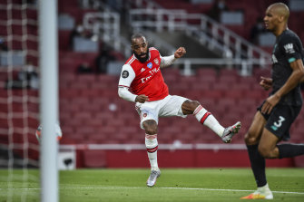 Arsenal's Alexandre Lacazette scores his team's first goal during the English Premier League soccer match between Arsenal and Liverpool at the Emirates Stadium.