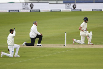 England and West Indian players and the umpires take the knee at the start of the first Test.