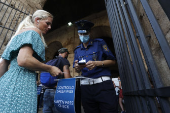 """Tourists have their """"green pass"""" checked by security staff at the entrance of the Colosseum in Rome, Italy, Friday, August 6, 2021."""