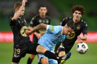 Melbourne City's Jamie Maclaren is challenged by Daniel Wilmering of the Wanderers on Friday night.