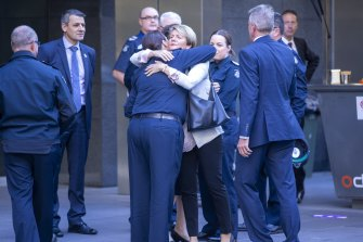Family members of the police officers gather outside court ahead of Pusey's sentencing.