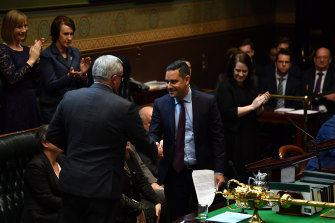NSW Health Minister Brad Hazzard congratulates Member for Sydney Alex Greenwich as he introduces the Reproductive Healthcare Reform Bill 2019 in the Legislative Assembly at NSW Parliament House on Thursday.