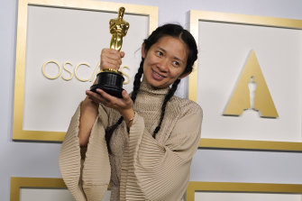 Nomadland director Chloe Zhao poses with one of her Oscars.