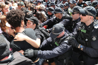 Police push back protesters outside the mining conference.