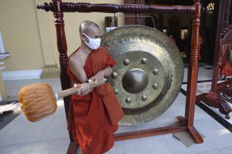 A Buddhist monk strikes a gong at a pagoda in Phnom Penh, Cambodia, to chase away the virus at the start of the pandemic.