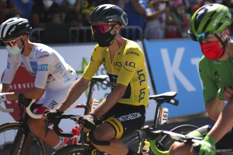A masked Adam Yates, from Australian team Mitchelton-Scott, wears the yellow jersey as leader of the Tour de France.